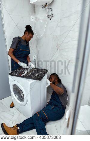 Portrait Of Young And Handsome Handyman Troubleshooting Washing Machine, Lying On Bathroom Floor. At