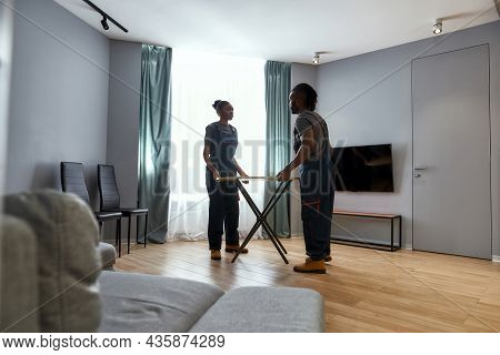 Young African American Woman And Man In Overalls Moving Wooden Table In Modern Flat. Moving Company