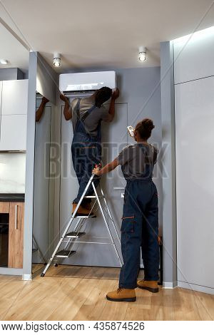 Back View African American Repairman Fixing Air Conditioner, Standing On Metal Ladder While African