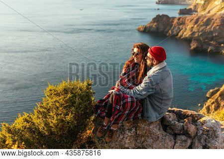 A Couple In Love At Sunset By The Sea. Wedding Trip. A Man And A Woman Embrace At Sunset By The Sea.