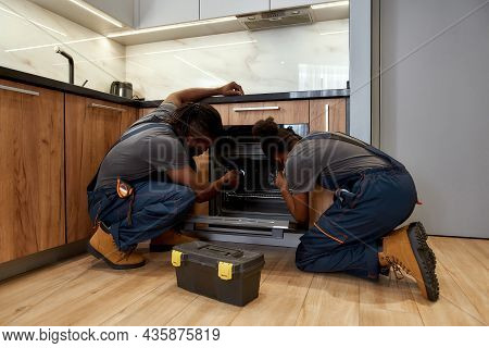 Back View Of Woman And Man In Overalls, Kneeling In Front Of Opened Kitchen Oven. African American R