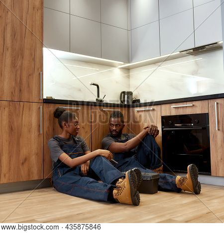 Two Multiethnic Man And Woman, Service Company Workers, Sitting On Wooden Floor In Kitchen After Fin