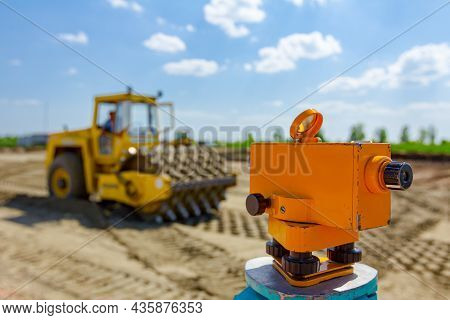 Surveyor Instrument For Measuring Level On Construction Site, Roller With Spikes Is Compacting Soil