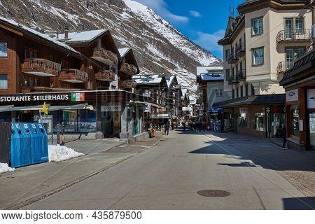 Zermatt, Switzerland - Circa 2021: People passing by on the streets of well-know mountain swiss resort town Zermatt. Winter scene with people passing by