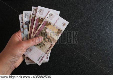 Russian Money In Hands. An Employee Holds Banknotes In Denominations Of 100 And 50 Rubles. Money Of
