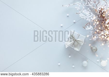 Christmas or New Year concept with gift box, festive baubles and snowy branch with pine cones on pastel background. Flat lay, copy space