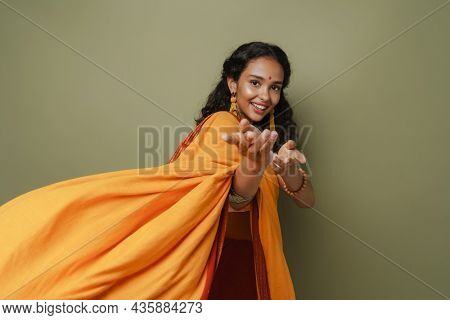 Young south asian woman wearing sari reaching her hands to camera isolated over green wall