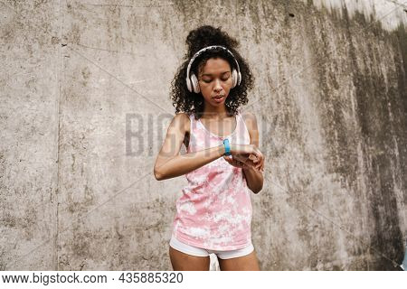 Young black sportswoman in headphones looking at her smartwatch while standing by concrete wall
