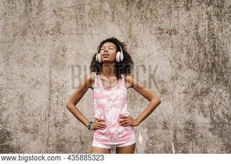 Young black sportswoman listening music with headphones while standing by concrete wall