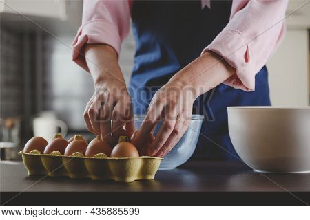 Woman Baker In Blue Apron Taking Eggs For Baking. Home Cozy Cooking Aesthetics.