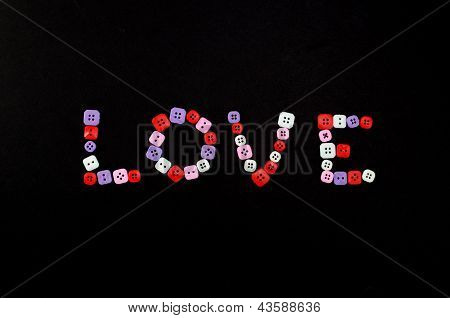 Red purple pink white buttons arranged to spell the word love on black background