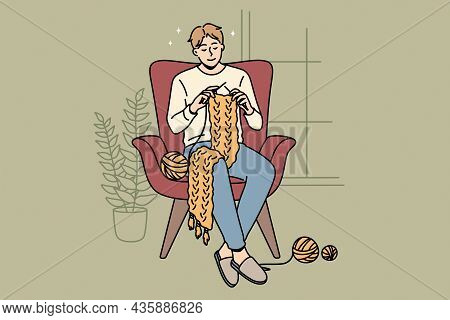 Home Hobbies And Knitting Concept. Young Smiling Man Cartoon Character Sitting At Home In Armchair K