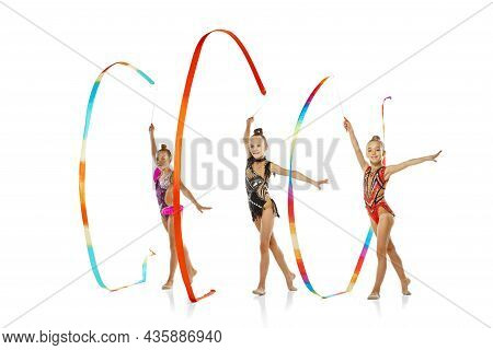 Three-ribbon Event. Portrait Of Little Beautiful Rhythmic Gymnastics Artists In Group Sport Event Is