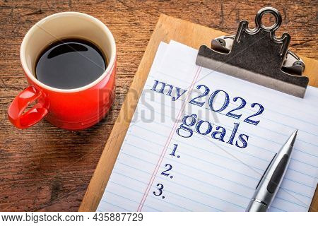 my 2022 goals list on clipboard and coffee against grunge wood desk, setting New Year goals and resolutions