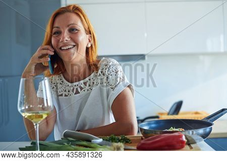 Woman cooking food while speaking on cellphone.Young woman cooking food in kitchen using cellphone. Cooking food lifestyle. Cooking food. woman cooking food at home while speaking on cellphone. Lifestyles. Healthy food cellphone Food cooking woman lifesty