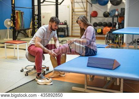 Physiotherapist helping young woman with prosthetic legs