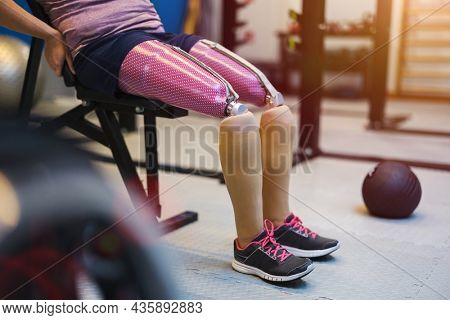 Close up of a woman with prosthetic legs exercising in the gym