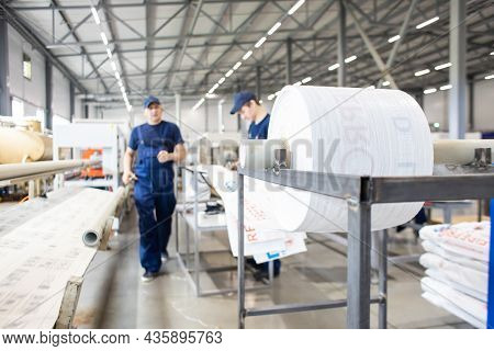 Workers In A Factory Carry Out Technological Processes On A Conveyor Line In Protective Overalls