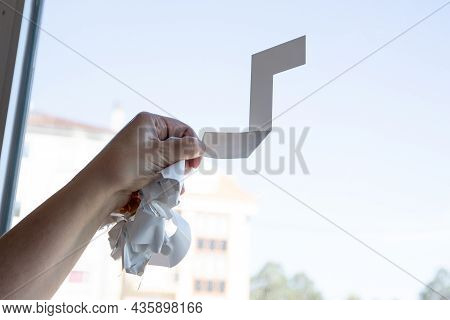 Close Up Of A Woman Hand Removing A Vinyl Sticker From A Window With A Tool. Copy Space
