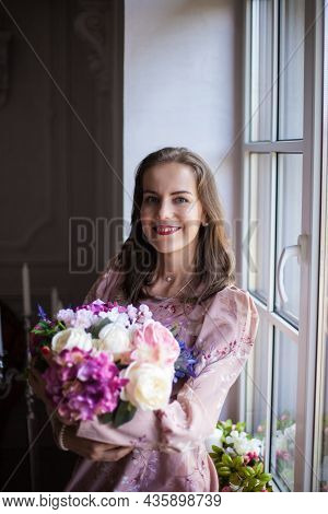 Beautiful Young Woman With Brown Hair And Red Lips, Dressed In A Pink Dress Sits On The Windowsill.