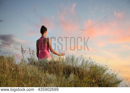 Woman Meditating In Meadow, Back View. Space For Text