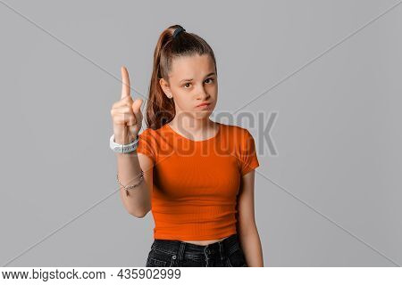 Serious Brunette Teen Girl Pointing Finger Up, Look Angry And Disappointed, Standing Over Gray Backg