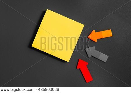 Yellow Square Blank Note And Three Small Arrows On A Gray Background. Short Note. Paper Stick Note