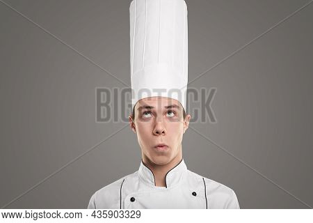 Hilarious Male Cook Wearying White Uniform And Hat Looking Up And Making Funny Face On Gray Backgrou