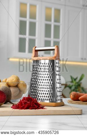 Grater And Fresh Ripe Beetroots On White Table In Kitchen