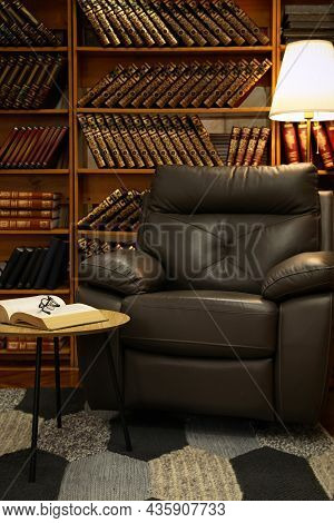 Cozy Home Library Interior With Leather Armchair And Collection Of Vintage Books On Shelves