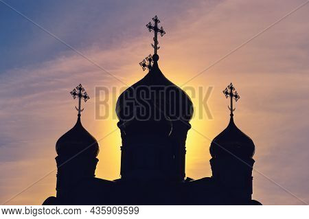The Silhouette Of An Orthodox Church With Crosses On The Domes. Sunrise At The Religious Building