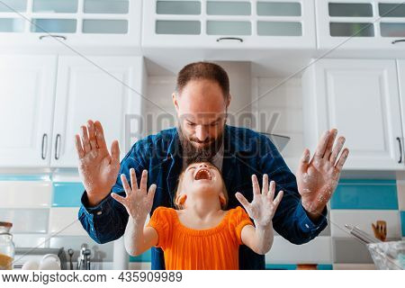 Little Girl Have Fun Playing With Dad While Cooking Baking In Kitchen. Daughter And Caucasian Father