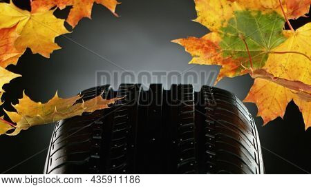 Car tire with falling autumn leaves, macro photo, weather concept. Studio photo, Free space for text.