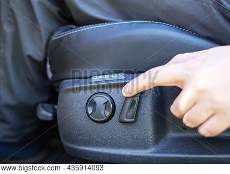 The Man Presses His Finger On The Adjustment Button For The Electric Seat In The Car. Modern Comfort