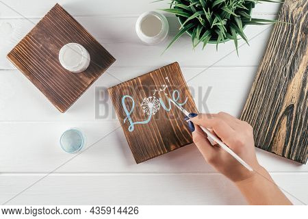 Womans Hand Draws Word Love And Dandelion Flower On Decorative Board Made Of Burnt Wood With Brush O