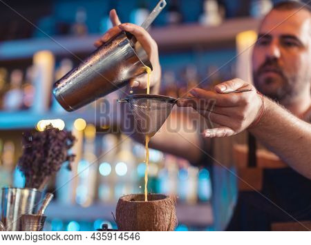 Bartender pouring juice using strainer in coconut shell in bar
