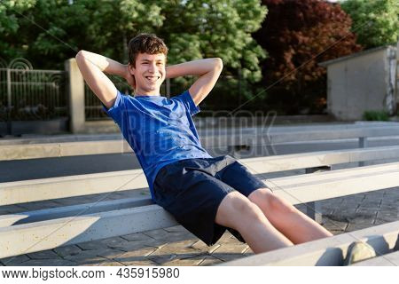 concept of sports and health - teen boy training abs muscles at the stadium. Pumping up abdominal exercise. Workout, fitness and health care.