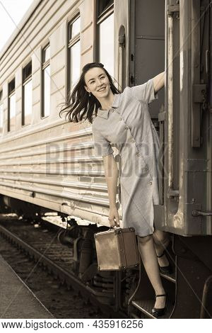 A Young Happy Woman Looks Out Of The Door Of A Moving Train. A Happy Woman Is Traveling By Train. Re