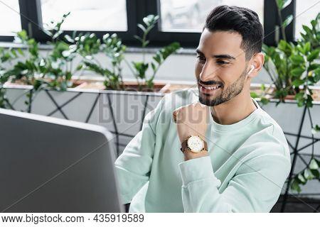 Positive Arabian Businessman In Wireless Earphone Using Blurred Computer