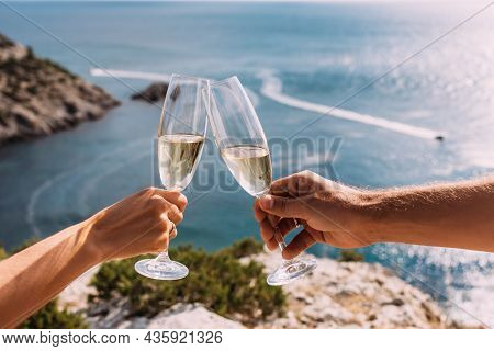 Hands Holding Champagne Glasses Over The Sea. Romantic Vacation. Two Hands Holding Champagne Glasses