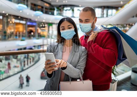 Millennial Multiracial Couple In Face Masks Checking Shopping List In Mobile App, Holding Shopper Ba