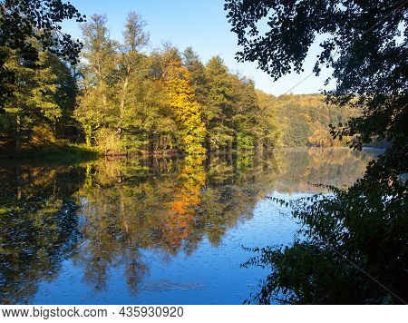Ohre River And Autumnal View Of Forest Mirroring On Water Surface Lake