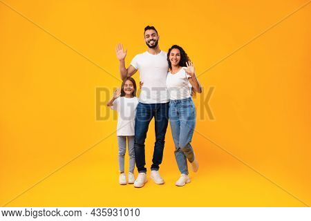 Middle-eastern Family Waving Hands Smiling To Camera On Yellow Background