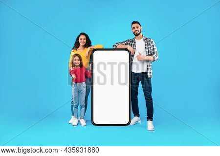 Middle-eastern Family Standing Near Full-length Phone Gesturing Thumbs-up, Blue Background
