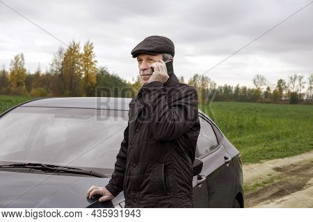 Adult Pensioner Stands Near Car And Talks On Smartphone Against Background Of An Autumn Rural Landsc