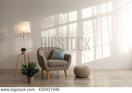 Comfortable Retro Armchair With Pillow, Luminous Lamp And Plant In Pot, Ottoman On Floor