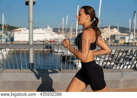 Side View Of Exhausted Young Sportswoman In Activewear Breathing Heavily And Running On Embankment N