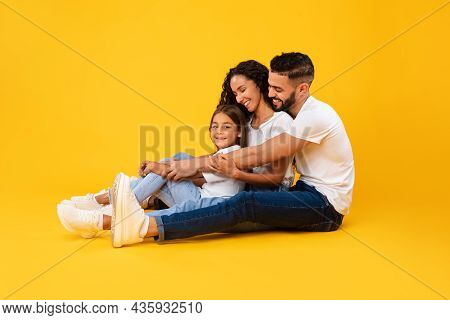 Side View Of Middle-eastern Family Hugging Sitting Over Yellow Background