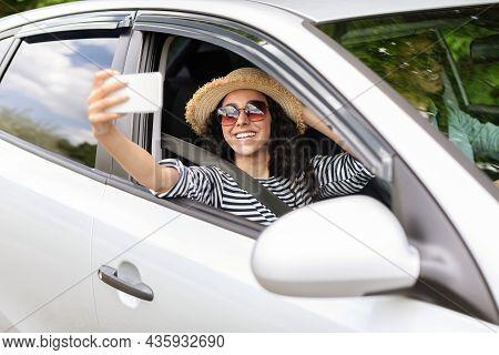 Pretty Middle-eastern Woman Enjoying Car Journey With Husband, Taking Selfie