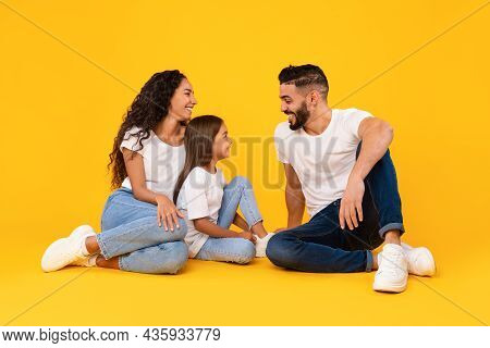Cheerful Middle-eastern Family Talking And Laughing Sitting Over Yellow Background